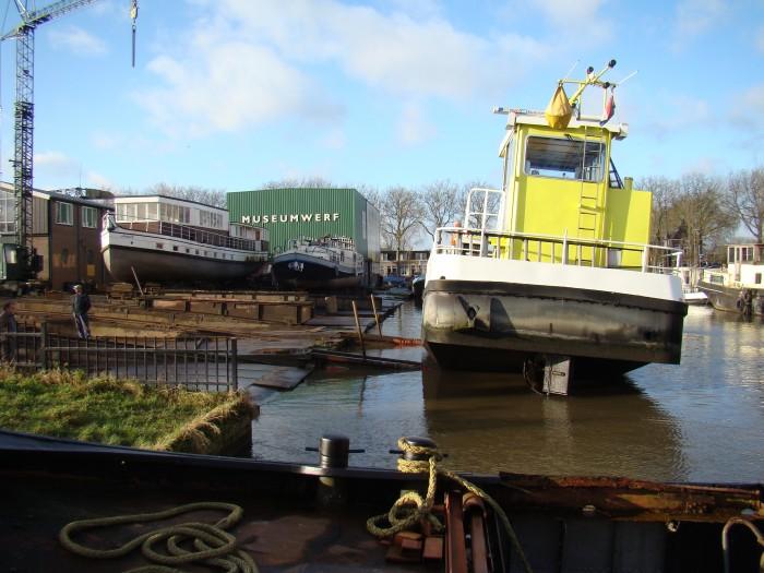 De Vrevia rijst uit het water. Op de achtergrond weer een andere oud-collega. Het is voormalig passagierschip Amandi die begin vorige eeuw op de lijndienst Leiden-Amsterdam voer voor de Leidsche Stoomboot Maatschappij De Volharding.